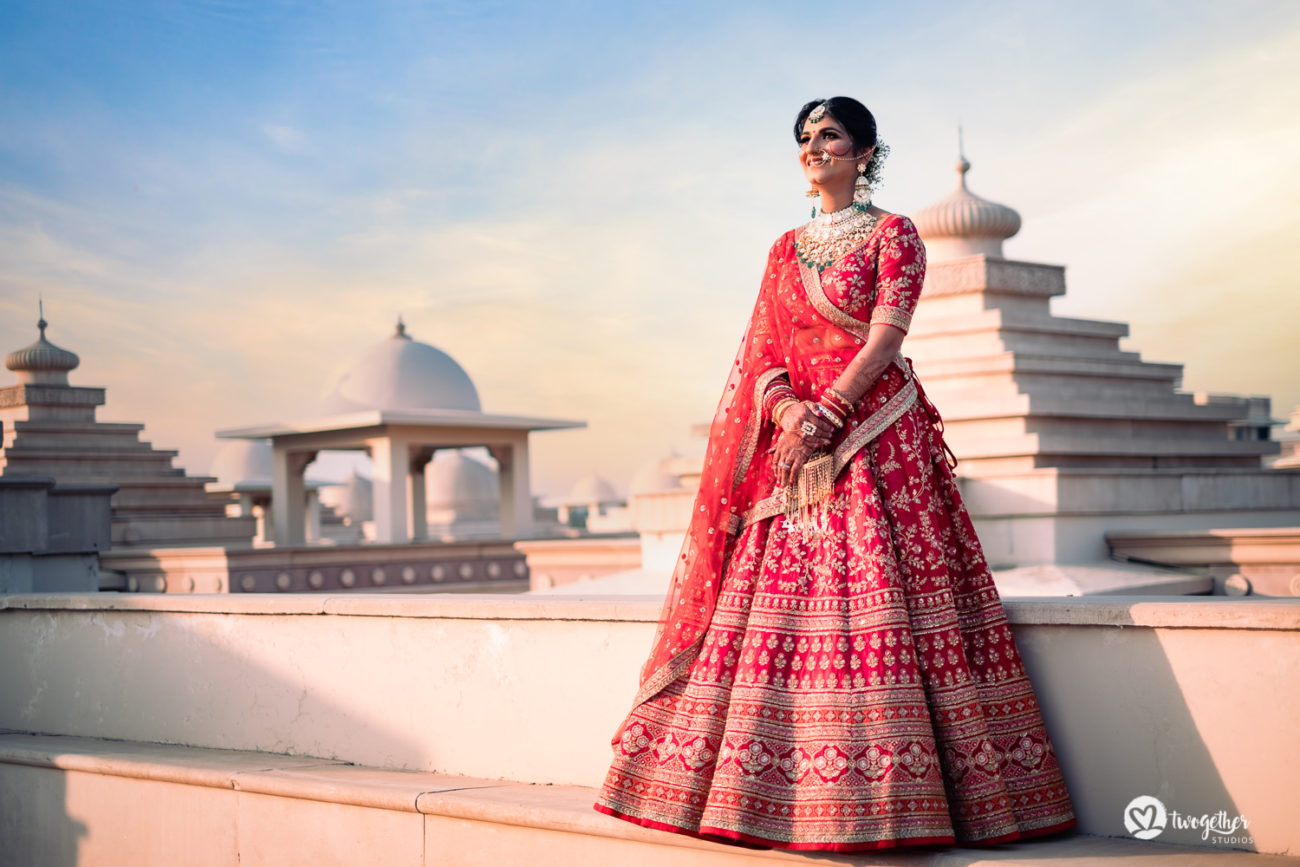Indian Sabyasachi bride in a red lehenga in an ITC Grand Bharat wedding.